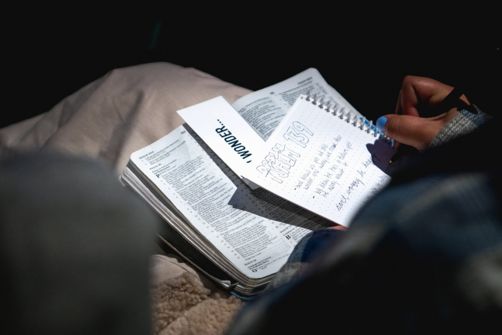 person holding bible with white notebook on it.